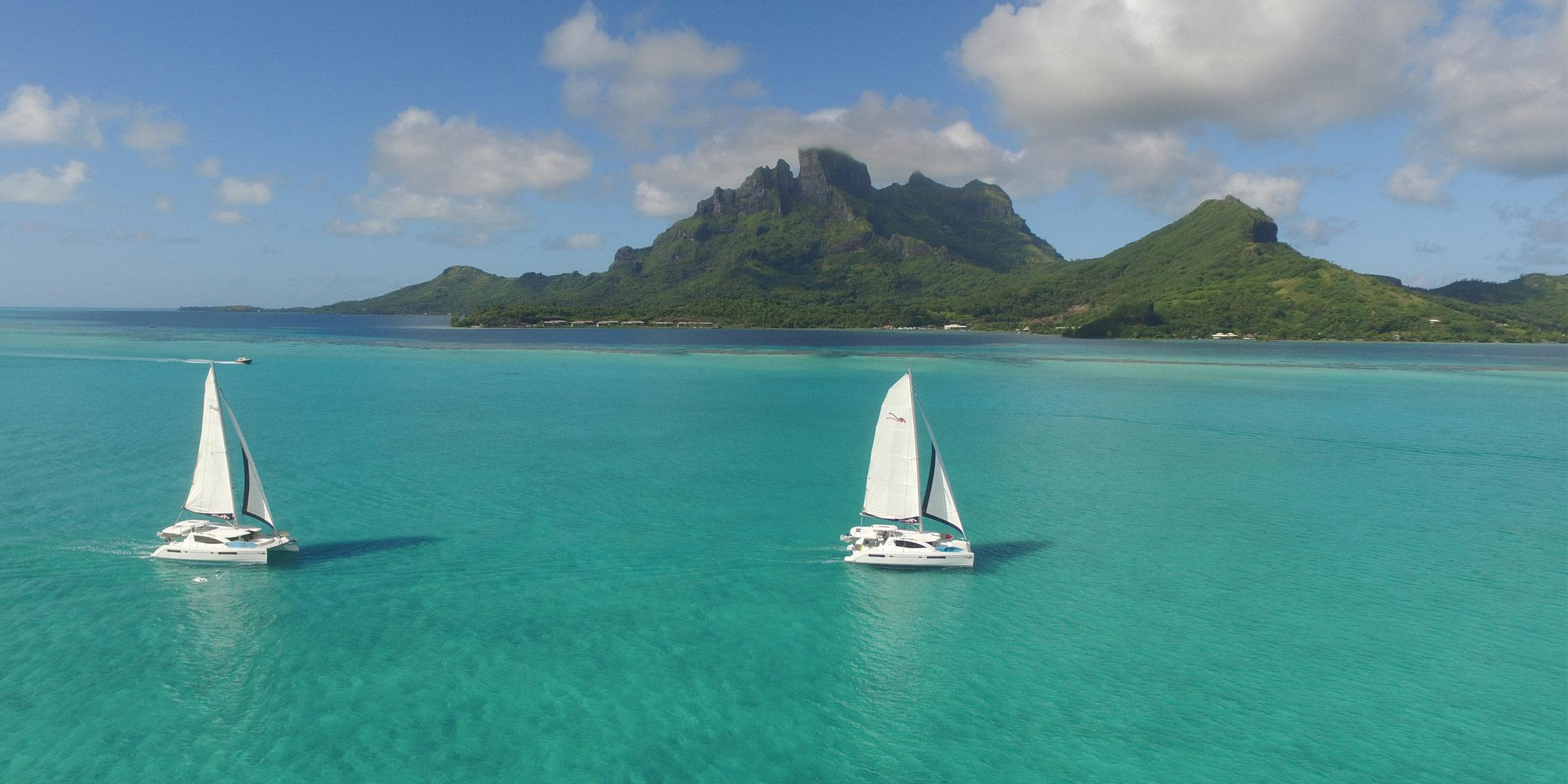 Two Moorings 4800 under sail with Bora Bora in the background